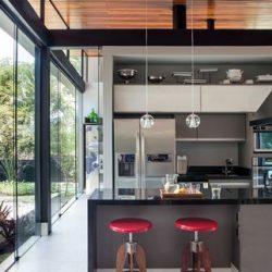 Casa em metálicas com cozinha aberta para jardim