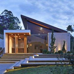 Residência térrea com fachada de vidro com telhado de uma água